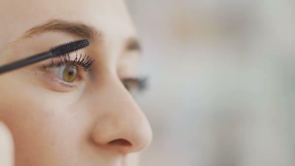 Close up of Beautiful woman doing makeup of eyes by black mascara, looking at mirror