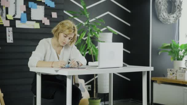 Business woman writes down something on stickers while sitting at the table