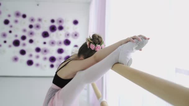 Little girls using ballet barre when doing leg stretching exercises in dance studio