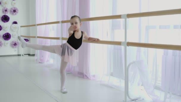 Little girl using ballet barre when doing exercises in dance studio