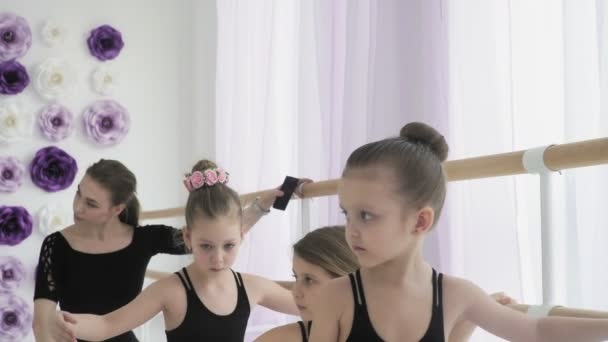 Close up of ballerinas are repeating the movements with the teacher.