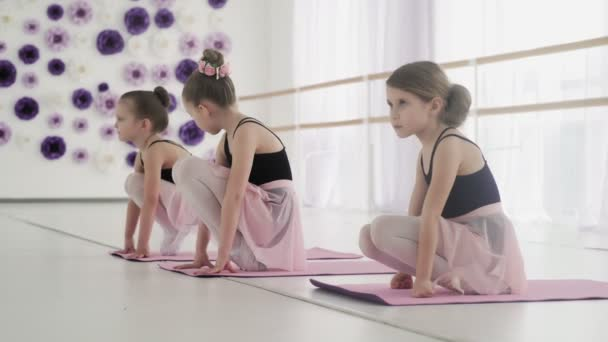Young ballet dancers doing stretching exercises on the floor