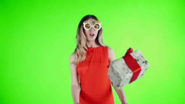 junge Frau in rotem Kleid mit lustiger Brille tanzt auf einer grünen Leinwand