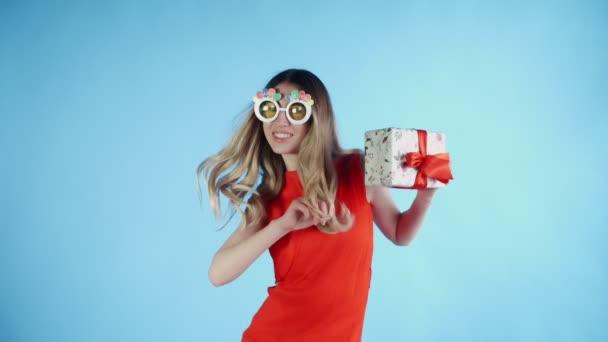 Fiatal nő vicces szemüveg és jelen a kezében táncol a kék háttér