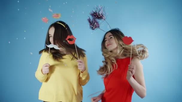 Schöne Mädchen in lustigen Hüten tanzen unter Konfetti auf blauem Hintergrund.