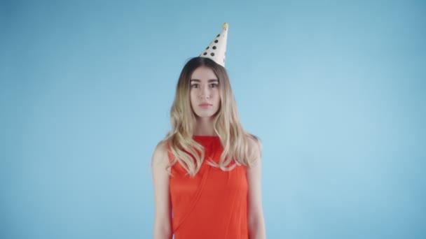 schöne Mädchen mit Partyhut stehen unter Konfetti auf blauem Hintergrund.