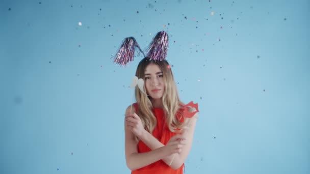 Gyönyörű lány fél kalap táncolnak alá konfetti és a lufi a kék háttér.