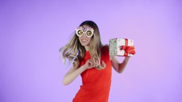 Fiatal nő vicces szemüveg és jelen van a kezében táncol a lila háttér