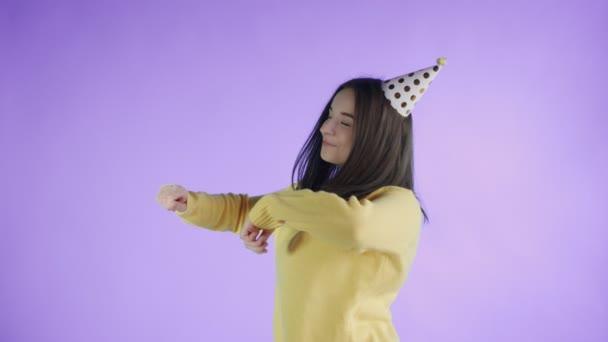 Fiatal nő sárga pulóver party kalap táncol a lila háttér