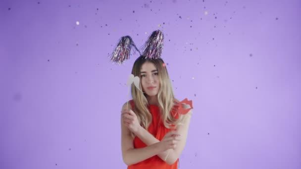 schöne Mädchen mit Partyhut tanzen unter fallendem Konfetti und Luftballons auf lila Hintergrund.