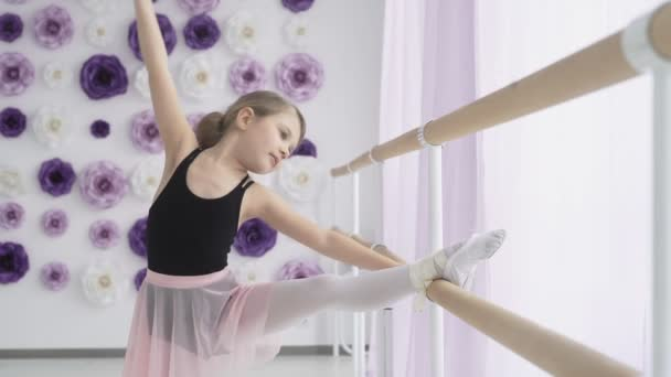 Little ballerina stretching while holding ballet barre