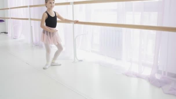 Young ballerina doing exercises near ballet barre in the studio.