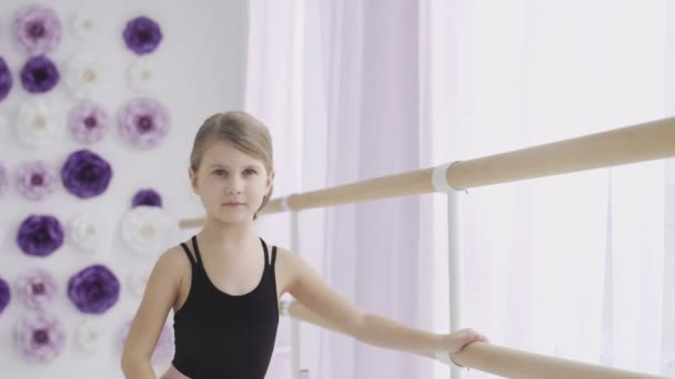 Close up of Young ballerina doing exercises near ballet barre in the studio.