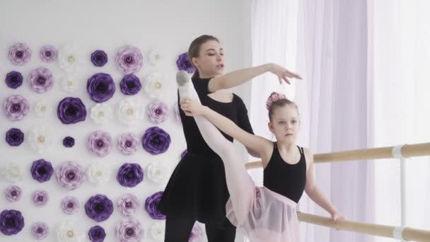 Ballettlehrerin professionelle Ballerina bringt Mädchen Beinbewegungen bei und beugt sich bei Ballettunterricht in der Tanzschule.
