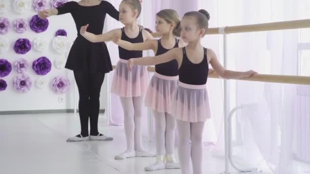 Dívky mají klasickou lekci baletu učí pohyby nohou s učitelem v ateliéru umění.