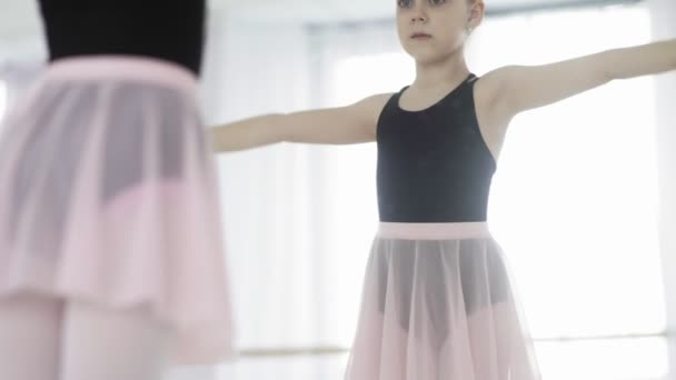Young ballerina looking at mirror and doing exercises