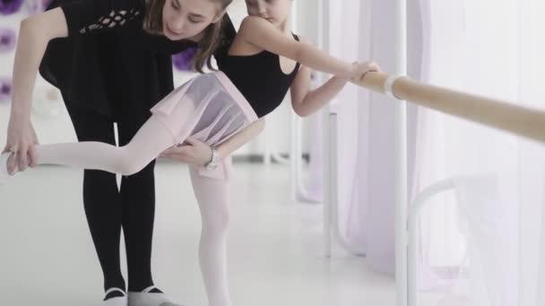 Balet učitel profesionální balerína je výuka dívky pohyby nohou a ohyby na baletní tyč