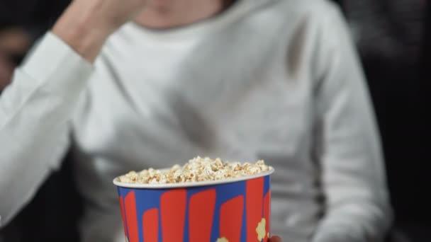 Férfi étkezési pattogatott kukorica a moziban, és nézi a filmet.