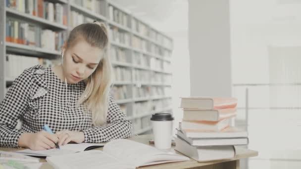 A nő papíron ír a könyvtárban.