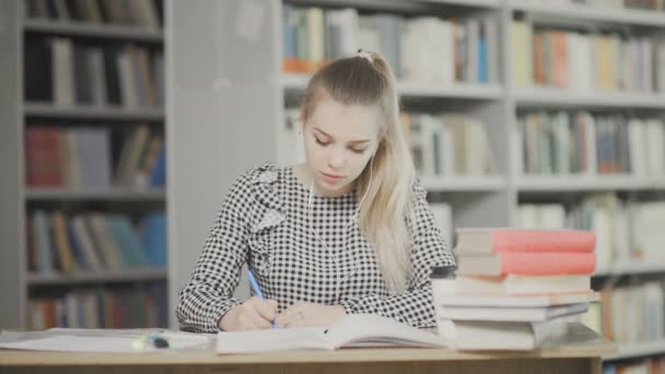 Portrait of girl student with headphones preparing for examination and writing notes while sitting at table at university library