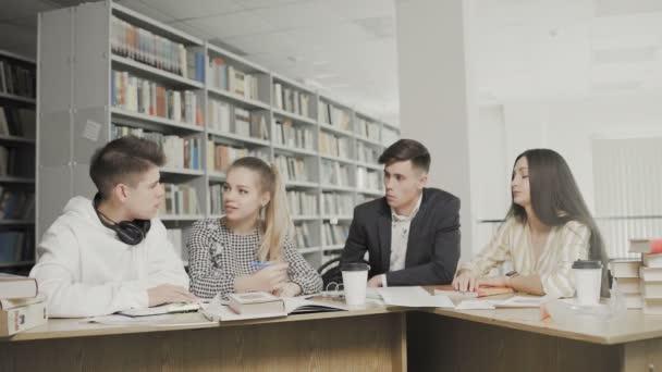 Dva muži a dvě ženy vysokoškoláci se smáli při přípravě na zkoušky, zatímco seděli u stolu v univerzitní knihovně