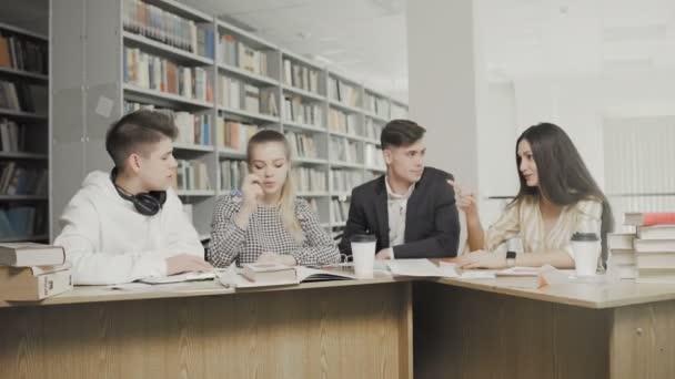 Mladí studenti chatují v univerzitní knihovně.