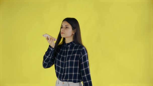 Photo Beautiful brunette woman records a voice message on her mobile phone on yellow Background in Studio