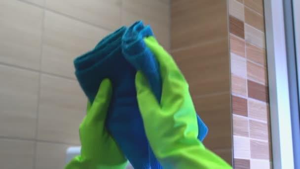 Žena v zelených rukavicích s modrou mikrofiber látkou čistí zrcadlo v koupelně.