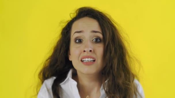 Porträt einer jungen schockierten, verängstigten und verängstigten Frau auf gelbem Hintergrund im Studio.