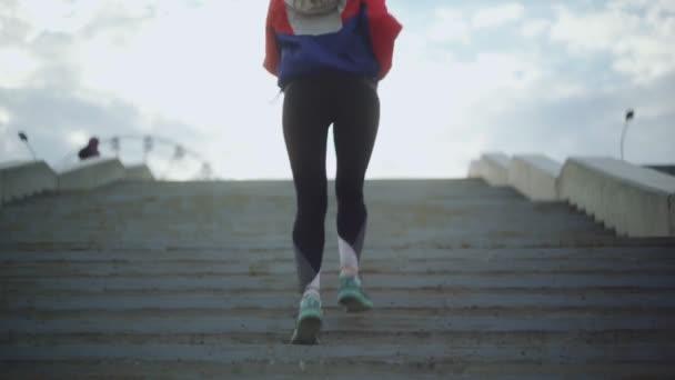 Zadní pohled na ženu ve sportovním oblečení běžící po schodech. Elegantní žena běží schody v parku sity.