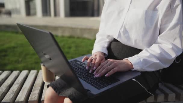 Fiatal üzletasszony ül a szabadban padon laptoppal és dolgozik.