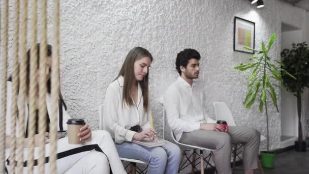 Állástalan üzletemberek pályázók csoport ül székek sorban sorakozó várja a sor vállalati állásinterjú