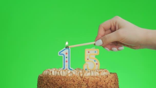 Dát číslo patnáct narozeninové svíčky na lahodný dort, zelená obrazovka 15