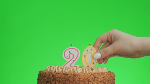 Putting a number twenty birthday candle on a delicious cake, green screen 20