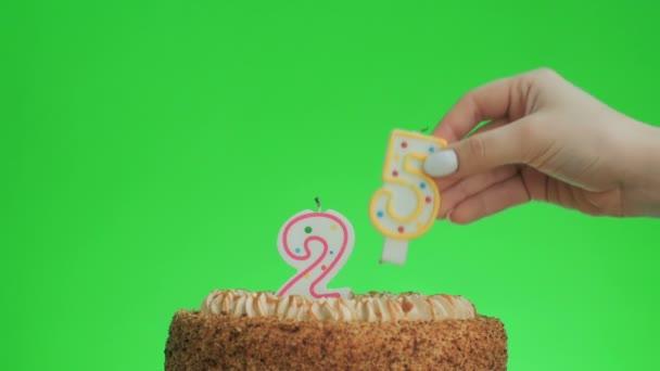 Dát číslo dvacet pět narozeninové svíčky na lahodný dort, zelená obrazovka 25
