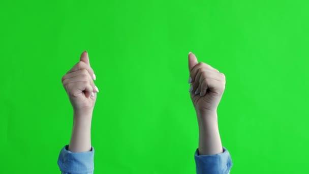 A nő keze csettint a zöld háttér felett. Fehér nő kezének csettintő ujjai