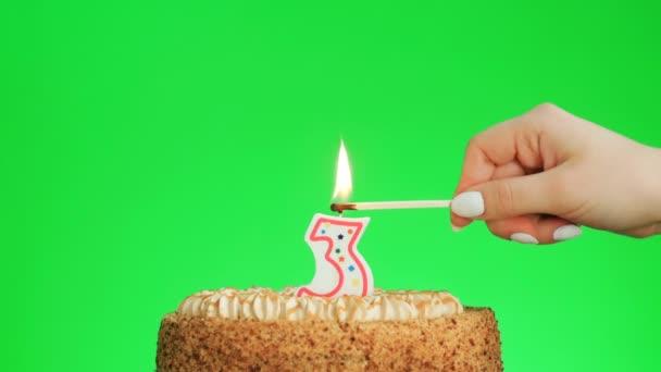 Meggyújtani egy hármas számú szülinapi gyertyát egy finom tortán, zöld képernyő 3