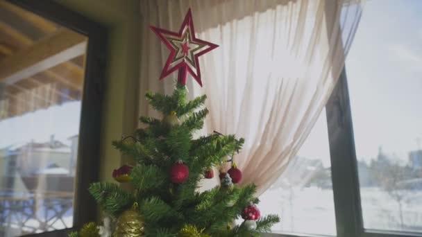 Velký vánoční stromek se zářícími světly, ozdoby a dárky v krásně zdobené domácnosti.