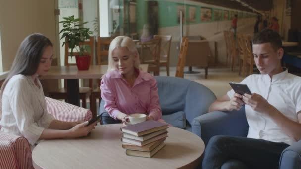 Két lány és egy férfi kávét iszik és könyveket olvas a kávézóban.