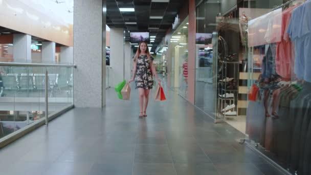 Fiatal ázsiai lány sétál bevásárló központ bevásárló táskák.