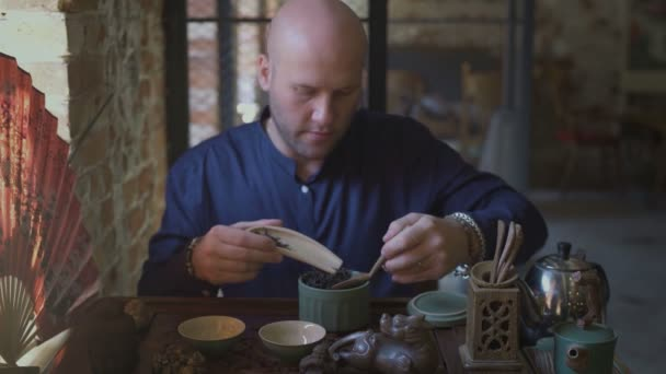 Bolde man doing a traditional chinese tea ceremony