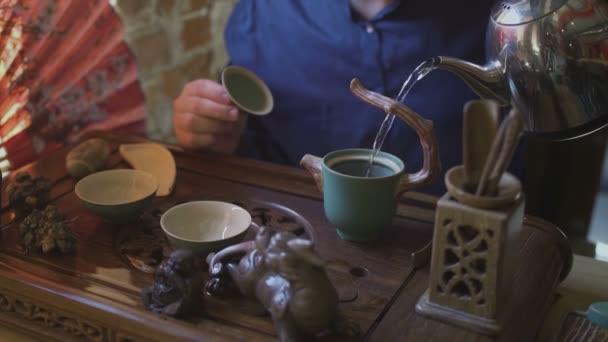 Muž nalévá horkou vodu do konvice. Čínský čajový obřad