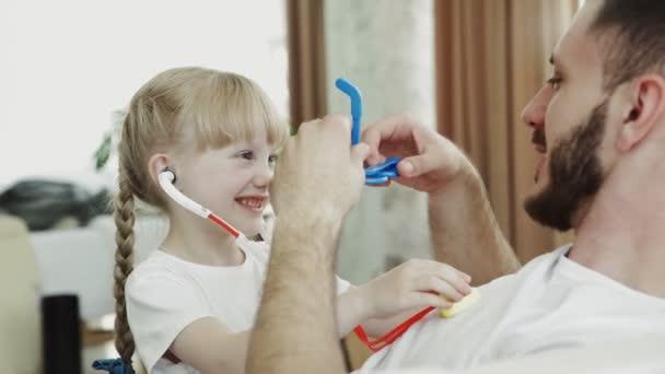 Kleines lustiges Mädchen in Arztuniform spielt als Arzt mit Vater zu Hause