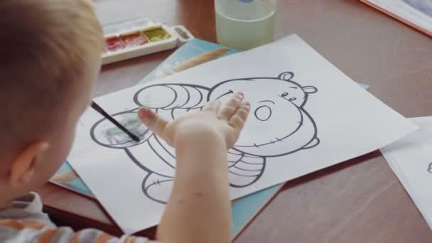 Chlapec kreslí hrocha v omalovánce