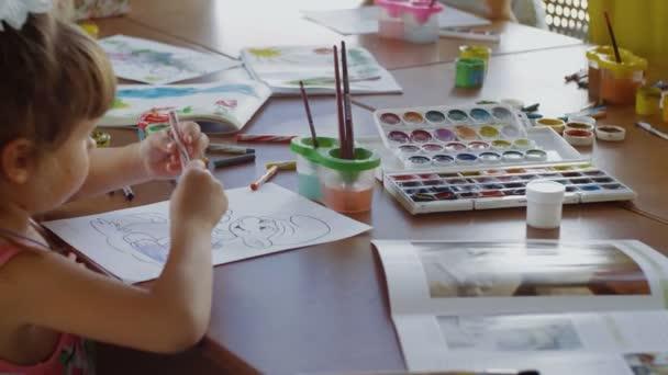 Malá holka kreslí gnóma ve školce.