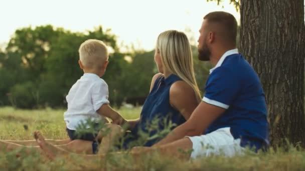 Šťastná rodina sedí na trávě a dívá se na krávy