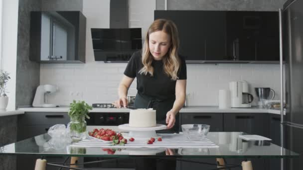 Profi-Koch kocht Kuchen. Junge attraktive Hausfrau bringt mit Metallspachtel weiße Sahne auf Schokoladenkuchen