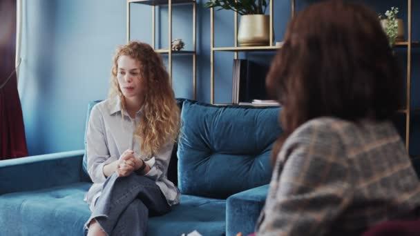 Rozrušená mladá žena sedí v uzavřené póze na pohovce a mluví s psychologem na terapii