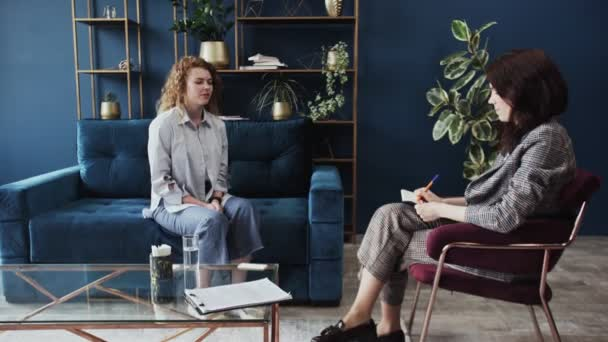 Young woman is talking to psychologist sitting on sofa in modern loft style studio. Psychologist listening to her and writing while patient is speaking explaining problem.
