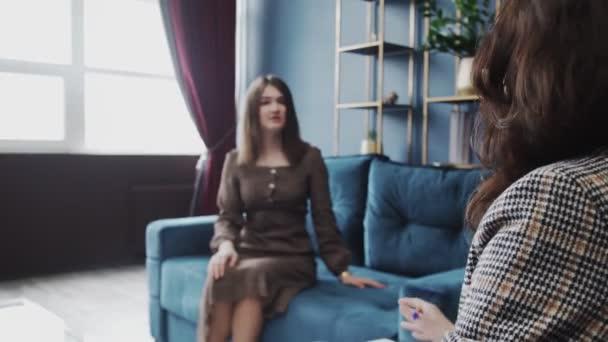 Zpětný pohled se zaměřením na psycholožku hovoří se ženou, která mluví a gestikuluje problémy se sdílením v úřadu. Pacient na rozmazaném pozadí
